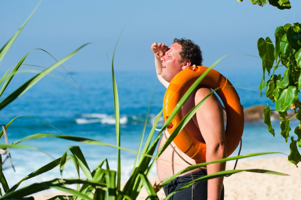 Man in hot sun on beach with life preserver
