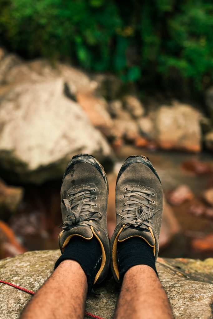 Dirty hiker boots putting feet up while taking a rest by a creek