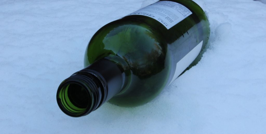 An empty bottle of wine in the snow