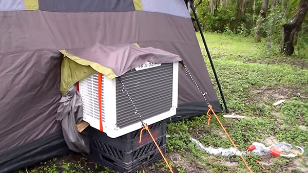 A tent with a vent hold for an outside window-mounted air conditioner